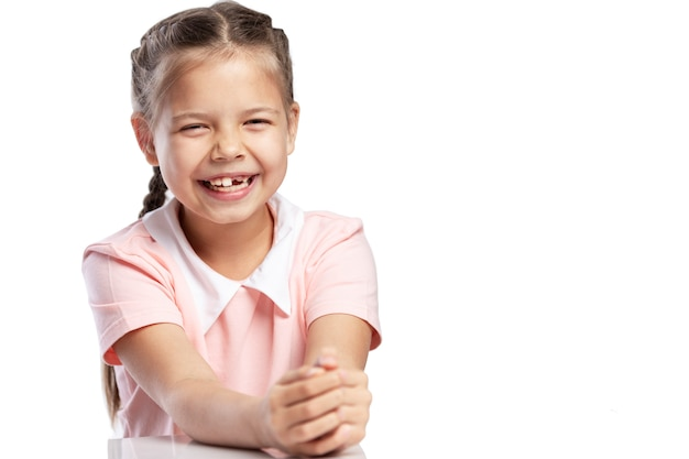 Een meisje in een roze jas van schoolleeftijd zonder voortand lacht. verandering van tanden. geã¯soleerd op witte achtergrond.