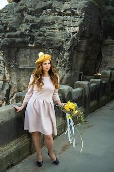 Een meisje in een roze jurk en een hoed met een boeket bloemen op het oppervlak van bergen en kloven in zwitsers saksen, duitsland, bastei.