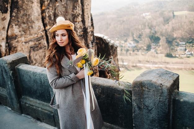 Een meisje in een roze jurk en hoed met een boeket bloemen tegen de achtergrond van bergen en kloven in zwitserse saksen, duitsland, bastey.