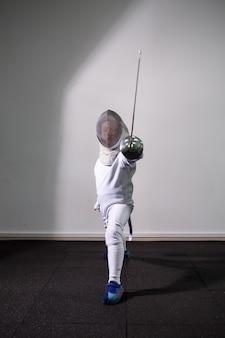Een meisje in een schermpak met een zwaard in de hand. jonge vrouwelijke model oefenen en oefenen. sport, gezonde levensstijl.