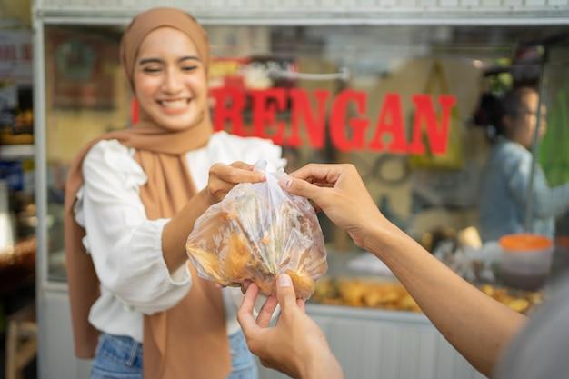 Een meisje in een sluier die gefrituurd eten verkoopt, geeft een gefrituurde bestelling