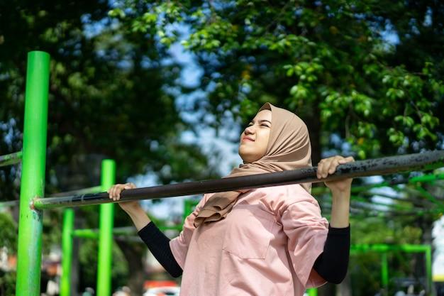 Een meisje in een sluier doet pull-ups om haar handspieren te trainen in het park