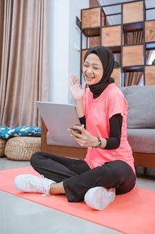 Een meisje in een sluiergymnastiekoutfit met een glimlach die een tablet bekijkt met een handgebaar van hallo zeggen na binnenoefening thuis