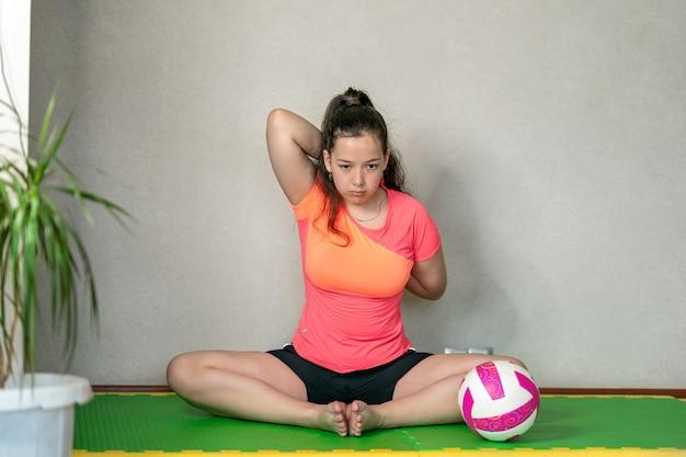 Een meisje in een sportuniform zit op een mat en doet stretching