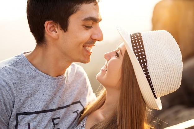 Een meisje in een stijlvolle hoed lachend en kijkend naar haar vriend die ook lacht