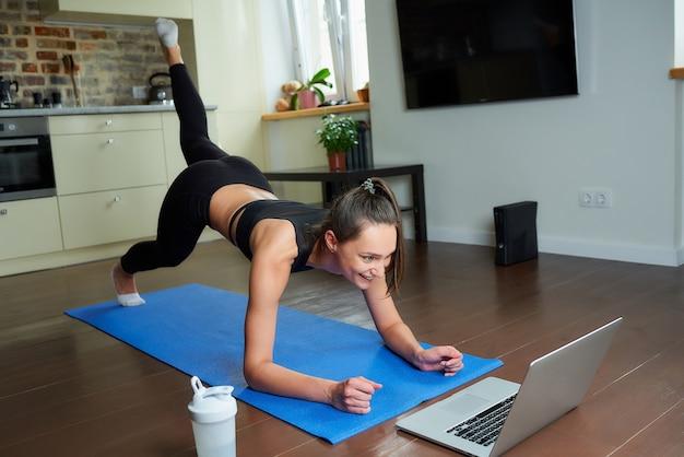 Een meisje in een strak trainingspak doet billentraining met een online video op een laptop.