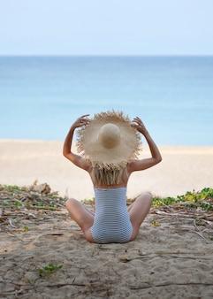Een meisje in een strooien hoed zit en heeft een gestreept badpak op haar tropische vakantie.