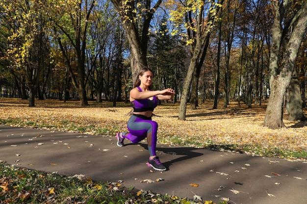 Een meisje in een trainingspak is aan het opwarmen in het park voordat ze rent. train in de frisse lucht