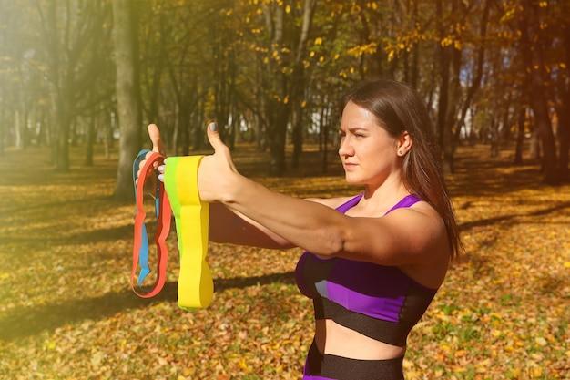Een meisje in een trainingspak kiest elastische banden voor training in het park