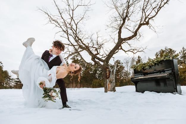Een meisje in een trouwjurk en een jonge man naast een piano in de sneeuw