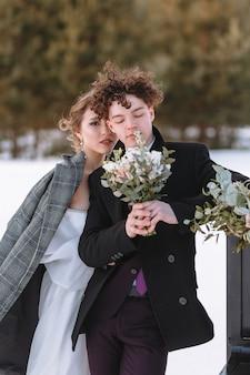 Een meisje in een trouwjurk en een jonge man staan naast de piano. winterfotografie in het bos