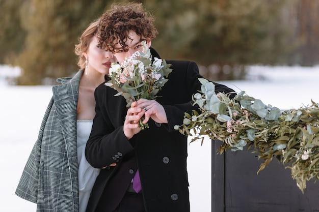 Een meisje in een trouwjurk en een jonge man staan naast de piano. winterfotografie