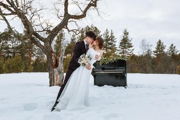 Een meisje in een trouwjurk en een jonge man staan naast de piano.