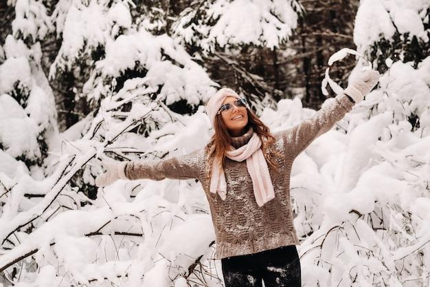 Een meisje in een trui en bril in de winter in een besneeuwd bos.