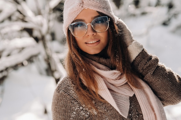 Een meisje in een trui en bril in de winter in een besneeuwd bos