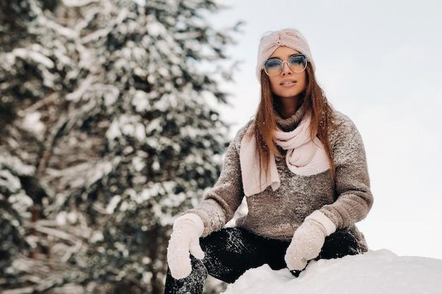 Een meisje in een trui en bril in de winter zit op een besneeuwde achtergrond in het bos.