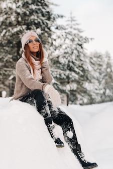 Een meisje in een trui en bril in de winter zit op een met sneeuw bedekte achtergrond in het bos.