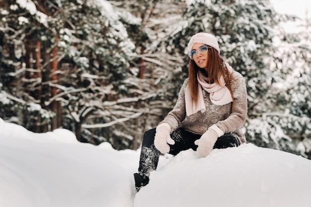 Een meisje in een trui en bril in de winter zit op een met sneeuw bedekte