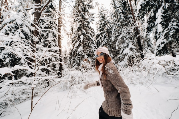 Een meisje in een trui en bril loopt in de winter in het met sneeuw bedekte bos.