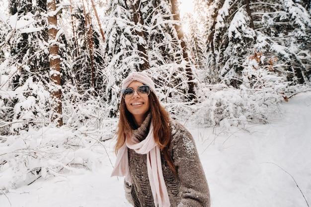 Een meisje in een trui en een bril loopt in de winter in het met sneeuw bedekte bos
