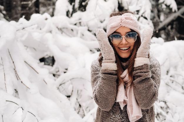 Een meisje in een trui en wanten in de winter houdt haar hoofd met haar handen in een besneeuwd bos.