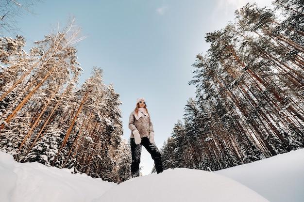 Een meisje in een trui en wanten in de winter staat op een besneeuwde achtergrond.