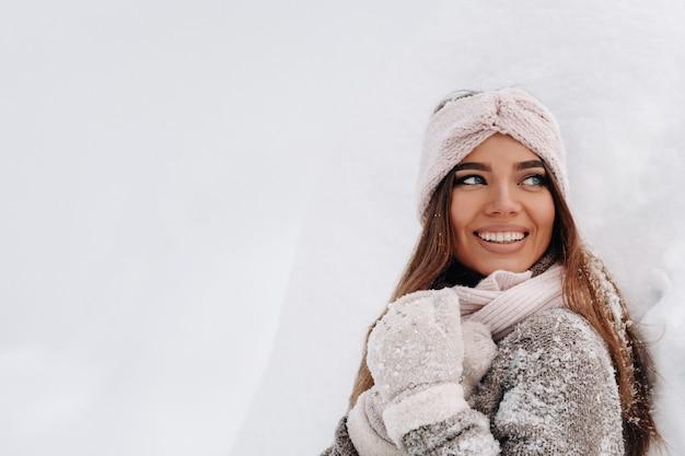Een meisje in een trui en wanten in de winter