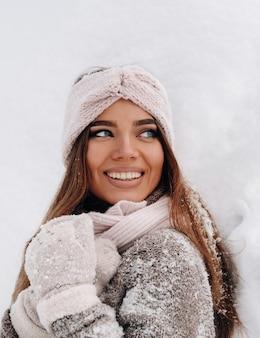 Een meisje in een trui en wanten staat in de winter op een met sneeuw bedekte achtergrond.