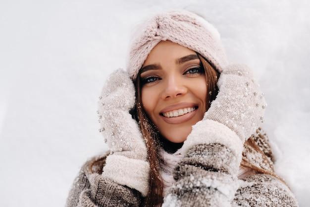Een meisje in een trui en wanten staat in de winter op een met sneeuw bedekte