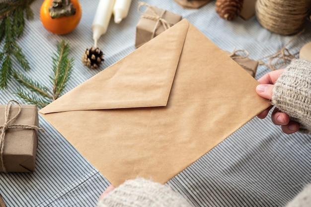 Een meisje in een trui houdt een ambachtelijke envelop vast op een nieuwjaarsoppervlak. het concept van een brief aan de kerstman, verlanglijst.