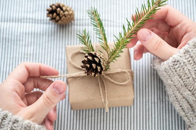 Een meisje in een trui houdt een geschenk vast dat met haar eigen handen is versierd. mooie geschenkdoos van kraftpapier, kerst of nieuwjaar. gift in handen van vrouwen, close-up.
