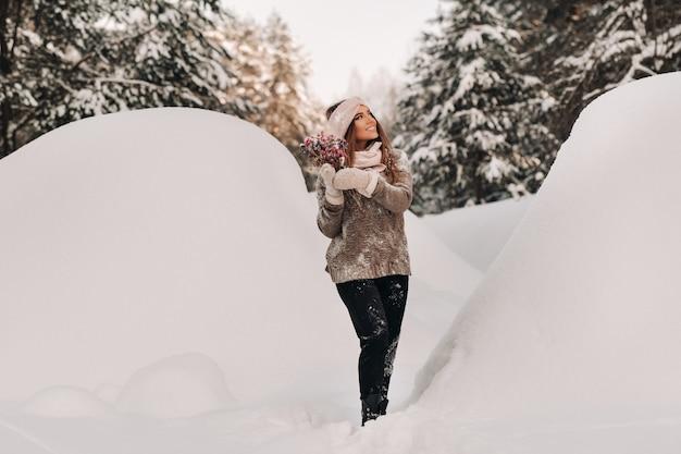 Een meisje in een trui in de winter met een boeket in haar handen staat tussen grote sneeuwbanken.