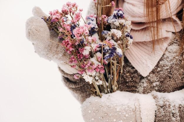 Een meisje in een trui in de winter met een boeket in haar handen staat tussen grote sneeuwbanken