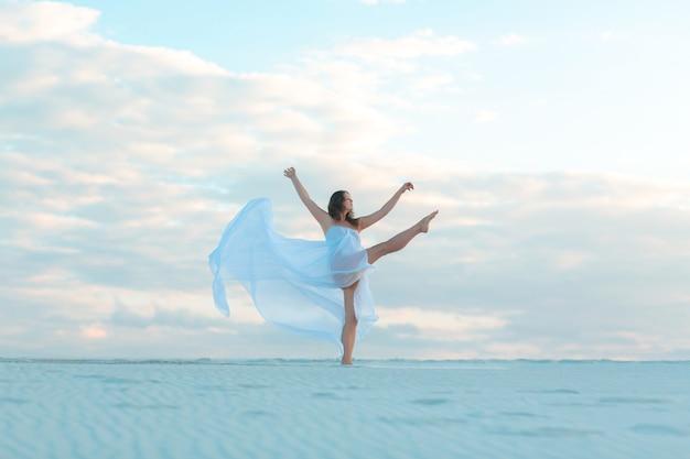 Een meisje in een vlieg witte jurk danst en poseert in de zandwoestijn bij zonsondergang.