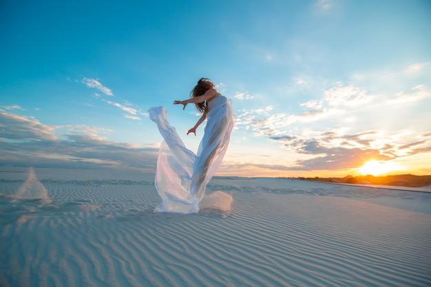 Een meisje in een vlieg witte jurk danst en poseert in de zandwoestijn bij zonsondergang
