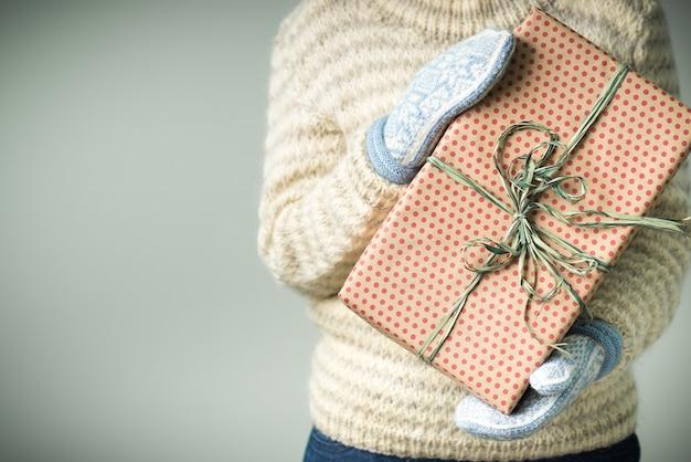 Een meisje in een warme gebreide trui en wanten houdt een kerstcadeau vast.