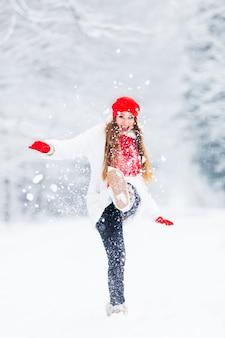 Een meisje in een winterjas en warme accessoires speelt met sneeuw