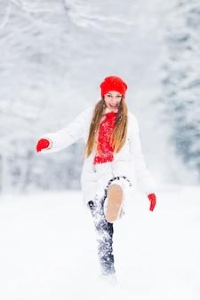 Een meisje in een winterjas speelt met sneeuw