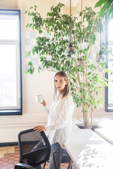 Een meisje in een wit shirt drinkt koffie in de pauze tussen het freelancer-werk.