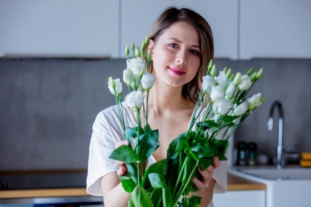 Een meisje in een wit t-shirt maakt een boeket witte rozen klaar voordat ze ze in een vaas op de keukentafel legt. levensstijl concept