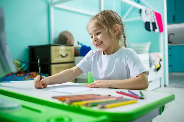 Een meisje in een wit t-shirt zit in haar kamer aan tafel en tekent met kleurpotloden