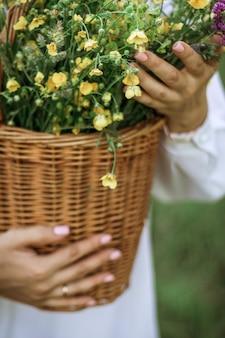 Een meisje in een witte blouse houdt een rieten mand met een boeket wilde bloemen vast. zomerwandeling in het veld. buik