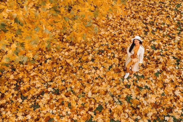 Een meisje in een witte jas en hoed glimlacht in een herfst park.portrait van een vrouw in de gouden herfst.