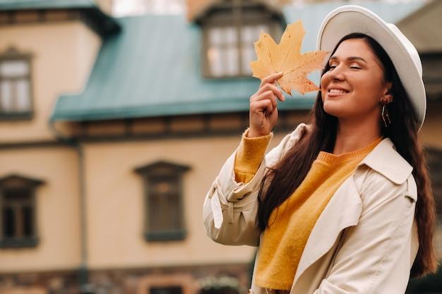 Een meisje in een witte jas en hoed glimlacht in een herfstpark