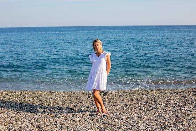 Een meisje in een witte jurk die langs de zee loopt