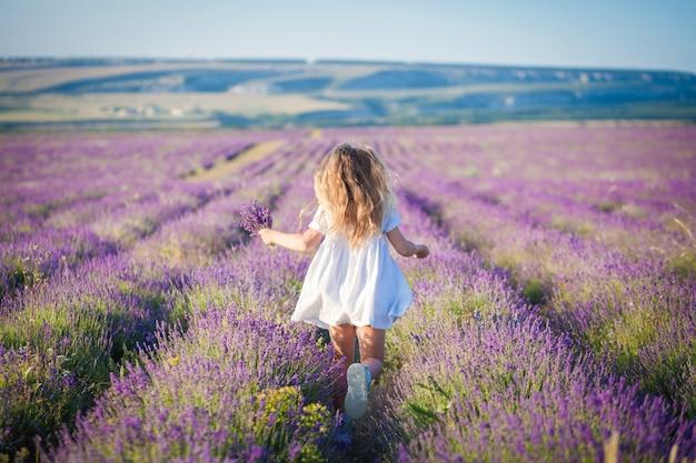 Een meisje in een witte jurk en een boeket in haar handen rent op een lavendelveld