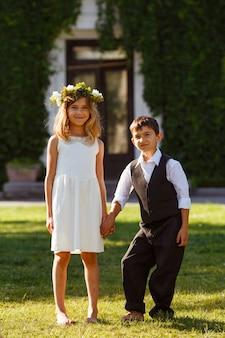 Een meisje in een witte jurk houdt de hand van een jongen in een modieus pak