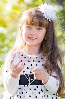 Een meisje in een witte jurk houdt een audio-hoofdtelefoon vast.