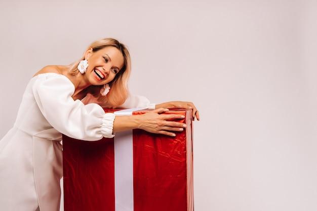 Een meisje in een witte jurk met een enorm rood geschenk op een witte achtergrond glimlacht.