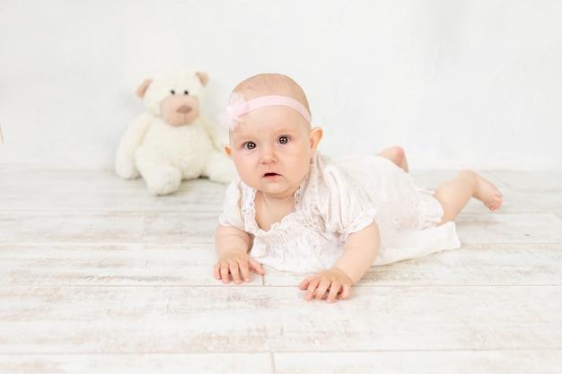 Een meisje in een witte jurk met een speeltje ligt zes maanden op haar buik